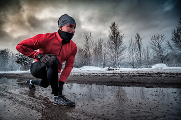 Runner man running in dirty puddle at winter, outdoor exercise