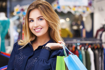Portrait of beautiful young woman with shopping bags in clothing store.