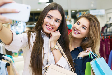 Young women taking selfie while out on a shopping spree.