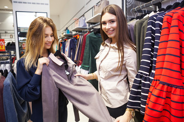 Young women shopping and looking at some clothing in a store