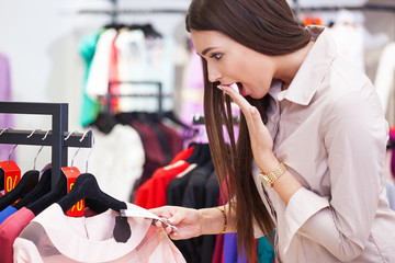 Young woman shocked by price while looking at some clothing.