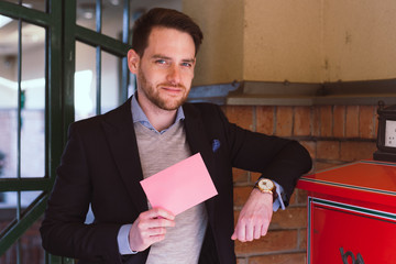 Handsome elegant man post a letter and show pink blank envelope on Valentines Day.