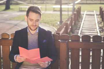 Handsome elegant man reading a love letter on Valentines Day.