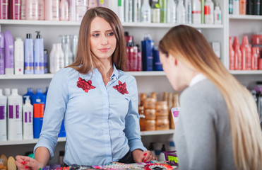 Impatient saleswoman looking at customer woman in beauty store