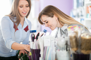 Customer woman choosing cosmetics with assistant in beauty store