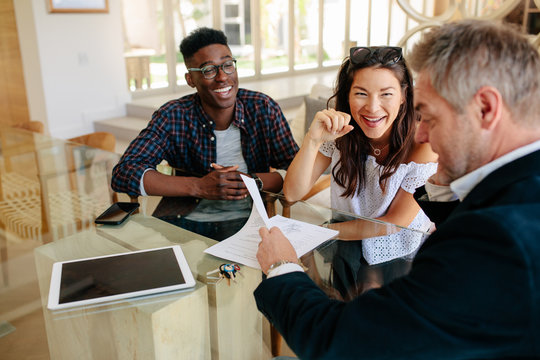 Realtor showing terms of contract to happy couple