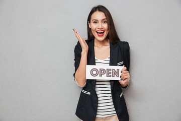 Cheerful asian business woman holding nameplate open