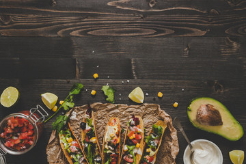 Mexican tacos with vegetables, salsa and avocado on the wooden background, top view