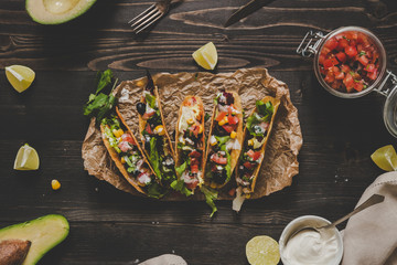 Mexican tacos with salsa and avocado on the wooden background, top view