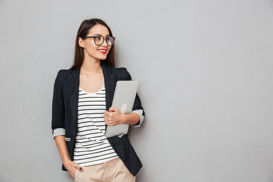 Smiling asian business woman in eyeglasses holding laptop computer