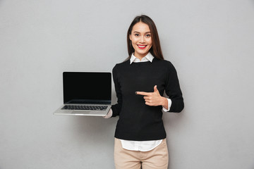 Pleased woman in business clothes showing blank laptop computer screen