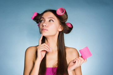 a young girl thinks about a fashionable hairstyle, on her head a big pink curler