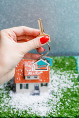 Picture of toy house with falling snow and hands with key