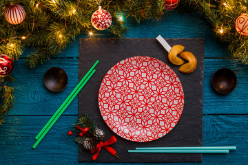 Photo of New Year branches of fir, black board, sushi sticks, prediction cookies,