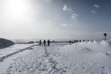 people in the far cold north walk around the snow-covered field