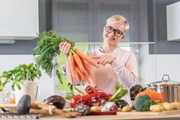 Freudig lächelnde Frau, zeigt in ihrer Küche auf einen Bund frischer Karotten