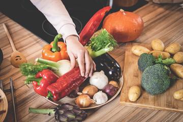Hand einer Frau nimmt Paprikaschote zum Kochen von mehreren Gemüsesorten
