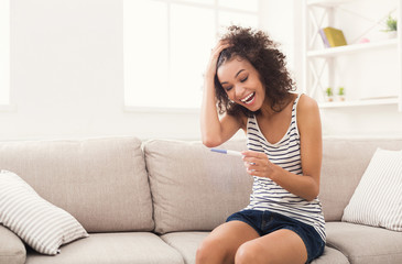 Excited girl reading results of pregnancy test