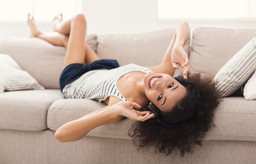 Happy young woman in headphones on couch