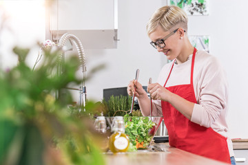 Smiling woman prepairing salad in the kitchen