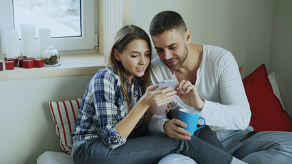 Happy young couple talking and browsing social media on smartphone while sitting in on bed and drink coffe in the morning at home