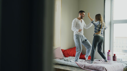Young beautiful and loving couple dancing rocknroll dance on bed in the morning at home