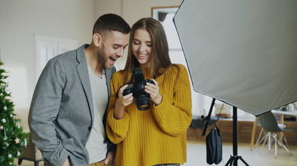 Professional photographer woman showing photos on digital camera to attractive model man in photo studio indoors