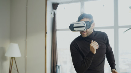 Excited young man with virtual reality headset dancing and play 360 video game at home