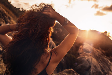 close up of beautiful young woman in rays setting sun