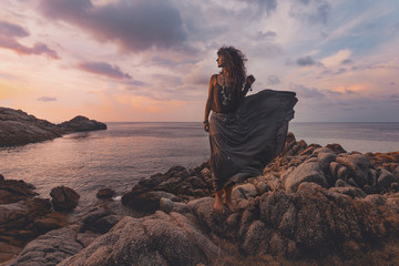 beautiful woman on the top of the rock at sunset over sea background