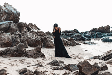 stylish young woman in elegant black dress on the stone beach
