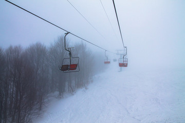 chairlift in misty mountains