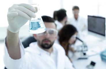 biochemist with flask Petri sitting at a Desk
