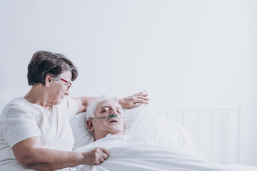 Elderly lady comforting her husband