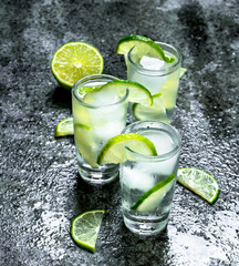 Vodka with pieces of lime and ice cubes.