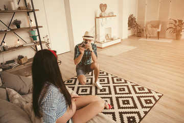 Man take a photo of pregnant woman in loft interior with old soviet camera.