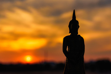 Silhouette buddha statues on blurred sunset background.Thailand.