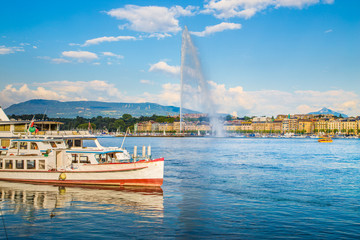 Geneva skyline with famous Jet d'Eau fountain and boat at sunset, Switzerland