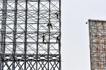 Workers under construction steel structure billboard.