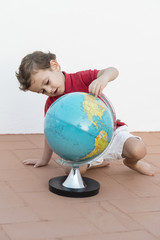 Child playing with a globe