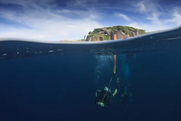 Scuba divers underwater half and half split over under photo