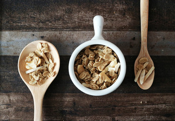 Granola spoon and cup isolated on wood table, top view