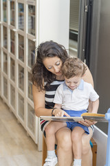 Mother and son reading a book.