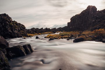 River Flowing from Waterfall over Volcanic Rocks Long Exposure