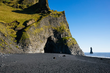 Man Stands below Rock Cave on Black Sand Beach