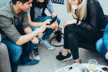 Group of friends millennials sitting outdoor bar using smart phone - technology, internet, happy hour concept