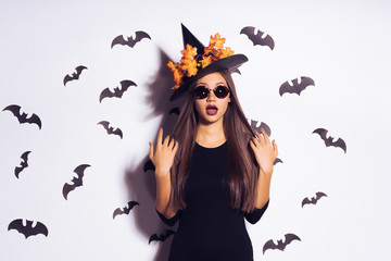 surprised young girl in the form of a witch for halloween, black clothes and a big hat