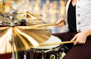 close up of woman drummer playing drum kit