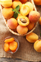Sweet apricots in basket and bowl on sackcloth