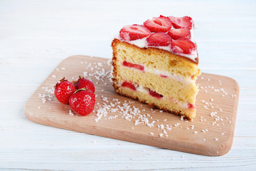 Biscuit cake with strawberries on white wooden table